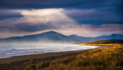 Light rays break though the cloud and onto Woodend Beach NZ