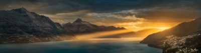 Sunset sunbeams hitting the Remarkables mountain range with Queenstown in the corner of this panorama