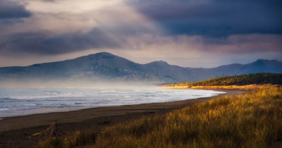 Sun rays streak through cloud onto Woodend beach, NZ